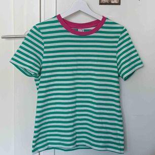 Vit och grön randig t-shirt ifrån & other stories i nyskick. Färgen är finare och har en starkare grön färg syns mer i verkligheten men är svårt att få med på bild.