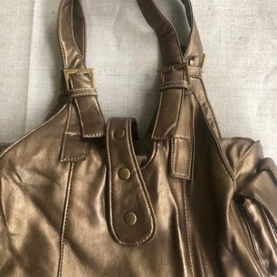 Ursnygg handväska i en bronzig/gulldig/metallisk färg🧡 Väskan är i ett bra, men användt skick och livar upp en tråkig outfit🥰 Köpt på humana secondhand. Pris är 50kr + frakt