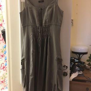 Ny oanvänd fin grå klänning med häftiga detaljer. Köptes förra sommaren, men storleken var f liten så den blev hängande i garderoben.