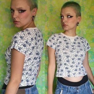 Benvit/beige blommig kortare t-shirt, blommorna är ljusare blå i verkligheten än på bild. I använt men bra skick, kan inte garantera äkthet då den är köpt secondhand. Frakten ligger på 44 kr, samfraktar gärna😊👍