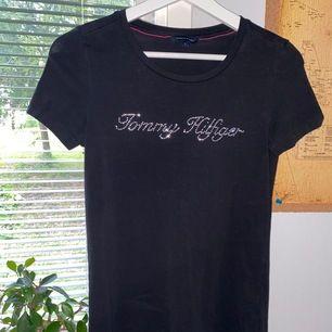 """Sjukt gullig t-Shirt från Tommy Hilfiger med små strass stenar som bildar texten """"Tommy Hilfiger"""" Den är i storlek S och nypris ligger på ca 600kr 💕"""