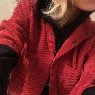 En röd tröja som liknar en skjorta, ganska liten i storleken!