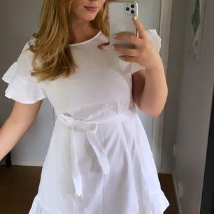 Vit sommarklänning med volang på ärm och nere på kjolen. Köpte en vit och en rosa, men väljer att behålla den rosa. Endast använd en gång under ett kalas. Alltså nyskick!! Så vacker, knyts i midjan för att framhäva midjan.
