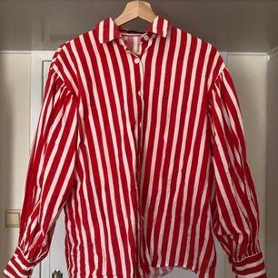 Röd- och vitrandiga skjorta med otrolig volym i puffärmarna! Mycket snygg instoppad i kjol eller byxor med hög midja. Avhämtning, eller skickas mot fraktkostnad.