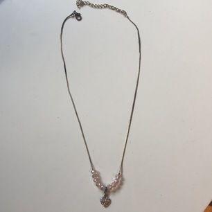 Halsband med hjärta och rosa pärlor. Kedjan är både ljus och mörk metall på.