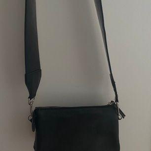 Liten svart väska från Åhléns, rymlig med massa fack, knappt använd. Bandet svart glansigt och är avtagbart! Frakt tillkommer