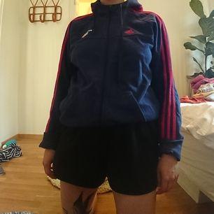 Mörkblå Adidashoodie med röda ränder. Iprincip oanvänd så i gott skick. Jag på bilden är 165 lång och har vanligen storlek s/m