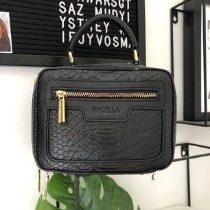 Stilren väska från märket Radella. Väskan är i ormskinnsimitation och har guldiga detaljer, finns öglor för att haka på ett väskband. Två olika väskband medföljer. Aldrig använd.