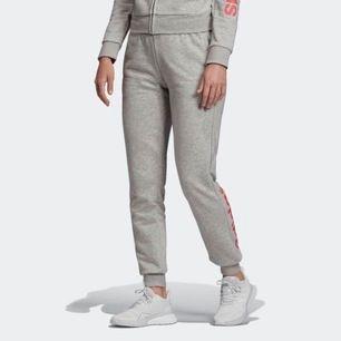 Mjuka sköna adidas mjukisbyxor med rosa text i Strl XS. Använda men i bra skick förutom 3 små sminkfläckar på ena benet (se bild 3). Nypris 399kr