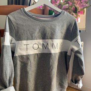 Grå sweatshirt från Tommy Hilfiger med snyggt tryck på både fram- och baksida. Säljer pga att den tyvärr har blivit för liten! Väldigt mysigt material på insida vilket gör den perfekt för höst/vinterväder! NYPRIS: 899kr