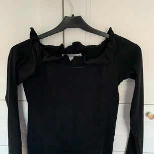 En svart långärmad off shoulder tröja som är ribbad, alltså små ränder på (se bild 3), och har små volanger runt. Storlek 158/164 som är XS. Använd 1-2 gånger så den är i bra skick. Säljer för 85 kr, frakt inkluderas i priset 🖤