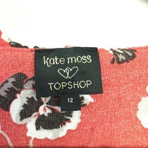 Sommarklänning från topshop i kollektion från Kate Moss. Kort klänning rosa/röd med blommor på. Passar S, omlott med snörning