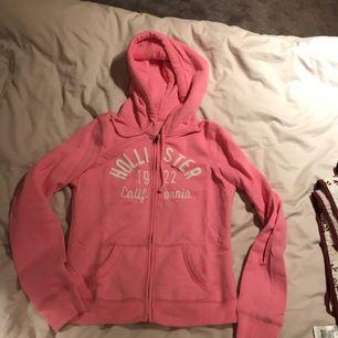 """Rosa hoodie från hollister. Köpt för några år sedan men knappt använd och i gott skick. Glittrig logga och finns """"lucka"""" för hörlurssladd i fickan!"""