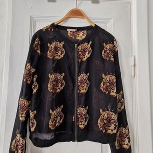 Jättefin svart tunn blusaktig jacka i polyester. Mexikanskt märke. Dragkedja i guld. Mönster med tigrar mot svart bakgrund. Mjuk och skön, tycker om den men använder inte tillräckligt ofta 🙃. S/M.