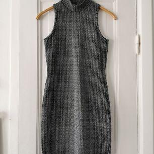 Snygg figurnära gråmelerad klänning med lätt polokrage.