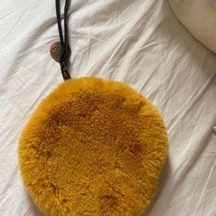 Jätte söt gul rund fluffig väska med öppning i sidan och svart läderband från lo-ika. Knappt använd så i väldigt fint skicka! 100kr inkl frakt