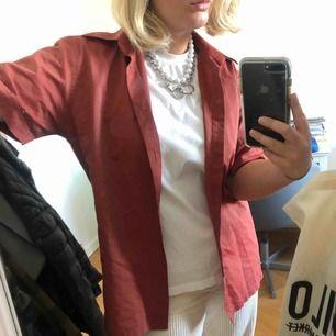 En kopparfärgad Sand skjorta med korta ärmar, as cool över en t-shirt med passande smycken!