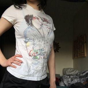 En skön secondhand vit T-shirt från T-POST med design som förseställer två personer som kysser varandra, om man vänder ut och in på t-shirten så står det lite om inspirationen till designen och om designern Esra Røise. Uppskattad storlek är S, Frakt 22 kr