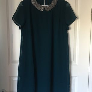 Short dress in petrol blue color with collar made of silver beads. Bought in Prague.