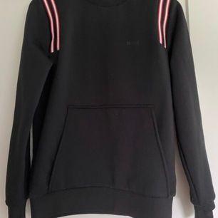 Säljer min Hugo boss Sweatshirt, den är i sportigt material, lite sliten på framsidan se bilder. Helt äkta köpt på boozt. Den är svart med röda axel detaljer.