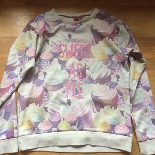 Sweatshirt i glansigt material med söta cupcakes samt texten