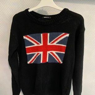 En svart stickat tröja med USAs flagga på från ginatricot. Frakt betalas av köparen.