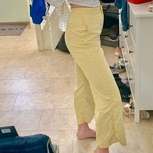 Läckra kostymbyxor i culottemodell. Somrig pastellgul färg. Både metallknäppen och plastknapp på insidan av gylfen. Ett bra och härligt material! Från H&M.