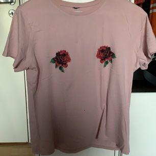 En ljusrosa t-shirt med rosor på från Ginatricot i strl S. Har använt den 1 gång🥰 (Uppdatering, såg inte det innan men det finns ett litet hål framme på tröjan som mitt bälte förmodligen gjort)