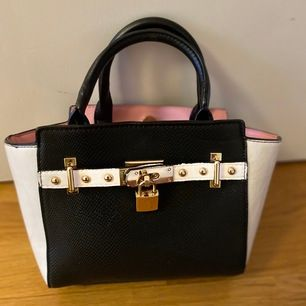 En jättesnygg River Island handväska i jättebra skick. Köpt på River Island förra året i London. Fint rosa silkestyg på insidan och fina gulddetaljer på utsidan. Höjd:14,5cm Längd:23,5cm Bottenbredd:6cm. Pris: 80kr+frakt. Pris kan diskuteras