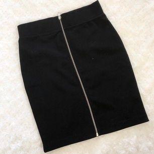 Svart kjol med silvrig dragkedja. Materialet är något stretchigt. I fint skick!