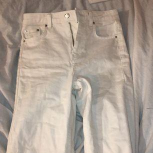 Ett par vita byxor med silvriga knappar. Slitningar längst ner på byxorna, sitter tajt vid höften men blir mer straight längre ner :) har använt typ 3 gånger