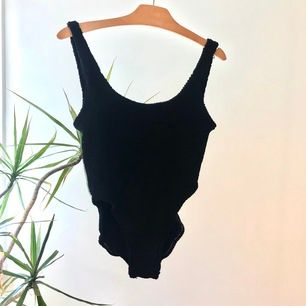 Suuuuperhögt skuren svart baddräkt med djup rygg i ett stretchiga typ räfflat material. Köpt second hand men jag har aldrig använt den. Hämtas i Linköping eller skickas mot frakt.