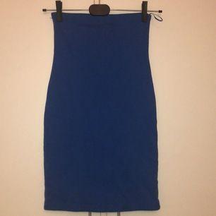 Väldigt figurformande mörkblå klänning från Gina. Det är dubbelt tyg i hela klänningen så man ser inget igenom. Den är en kort modell så man skulle kanske t.o.m. kunna ha den som en längre kjol.
