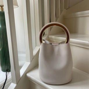 Vit somrig väska med trä och guldetaljer! Rymlig väska som är perfekt nu till sommaren. I gott skick använd ett fåtalgånger, dock lite sminkfläckar i väskan( se bild) men det är inget som syns✨