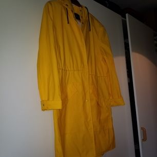 Klassiskt gul regnrock i typ nyskick. Snören i midjan och huva!