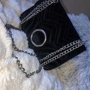 """Kedjan på denna väska går att justeras så man kan både ha den som en axelväska samt en """"lång och hängande"""" väska. Helt oanvänd."""