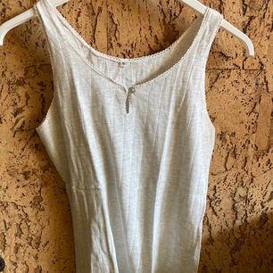 Ljusgrått, småribbat linne från 80-talet, äkta retro! ❣️ Fint skick trots sin ålder, perfekt i sommarvärmen ☀️ Köparen betalar frakten, kontakta mig vid frågor/fler bilder ✨