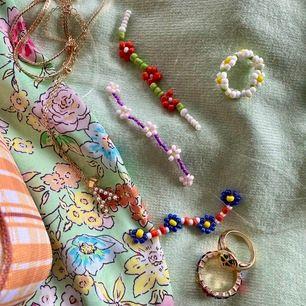 Handgjorda smycken i blommönster. Går att få i både ring, halsband och armband. Anpassar färg och mönster efter önskemål, på bilden är exempel på mönster och färger. Pris varierar beroende på ring, armband eller halsband.