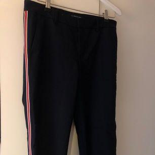 Marinblåa kostymbyxor från zara woman i storlek 36. Dom är lite större i midjan (finns hål för skärp). Vita o röda detaljer på sidan av benet. Använda ett par gånger men väldigt fint skick. Orginalpris va 500kr. Säljer för 100 kr, frakt tillkommer.