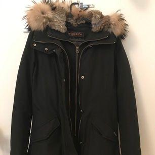 Svart Woolrich vinterjacka i storlek S. Använt den endast en vinter, därmed normalt slitage annars mycket bra skick. Säljer då den är lite stor för mig för i vanliga fall har jag XS i allt och är ganska kort. Ord pris 8900kr från Johnells. Säljer för 4500