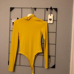Gul body, endast använd en gång.  Som man ser på bilden är det string body så den syns ej under byxor, kjol osv.