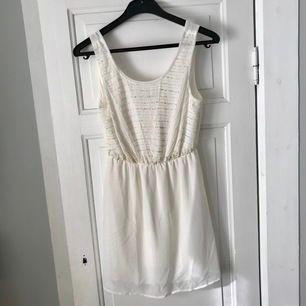 Vit klänning med pärlor på överdelen (framsidan), storlek XS från Gina Tricot. Fint skick. Frakten ej inräknat i priset.
