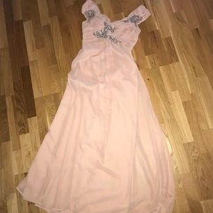 Denna klänning kan användas till bal eller bröllop ex.  Den har en ljus gammelrosa färg med silvriga stenar, paljetter som detalj på överdelen