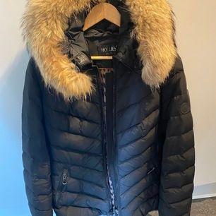 Hollies vinterjacka med äkta fin päls som går att ta bort så man kan tvätta jackan. Liten skada som är sydd vid höger ficka, syns knappt, annat super fin och fint skick