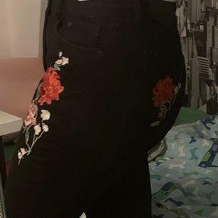 Oanvända svarta jeans från H&M med broderade rosor på. Aldrig använda då de är för korta och för små :( Står stl 42 men tycker de borde passa 38/40