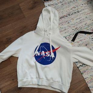 Croppad hoodie från H&M med NASA-loggan på framsidan och ena ärmen. Endast använd 2 gånger och i jättefint skick! Frakt betalas av köparen.