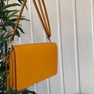 """Gul Axelremsväska från H&M i nyskick. Väskan har två stora fack samt ett """"hänge"""" med en nyckelring för dina nycklar. Endast använt ett fåtal gånger därav det fina skicket. Säljer för 100 kr. Köparen står för frakten (:"""