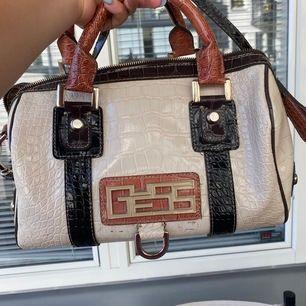 En glansig guess väska med krokodil skin och har även ett längre band som man kan ha över axeln ! Orginalpris : 980 , bra kap till en sån dyr väska 💫