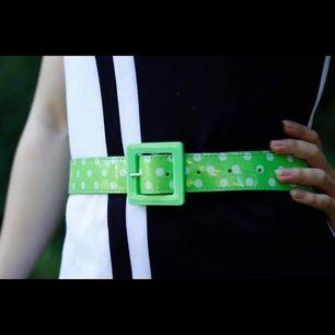 Limegrönt lackskärp med vita prickar & kantigt plastspänne. Gott skick (använt 1 gång).  Finns för avhämtning i Malmö, alt kan skickas (mot att köparen betalar frakten). Be