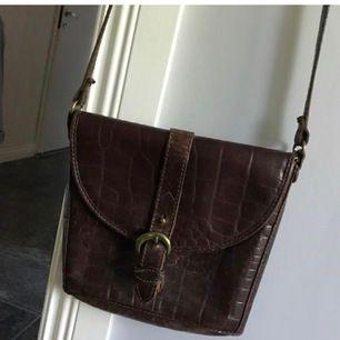 Snygg brun vintage läderväska med fina detaljer från märket THE TREND. Passa på att fynda denna unika väska!